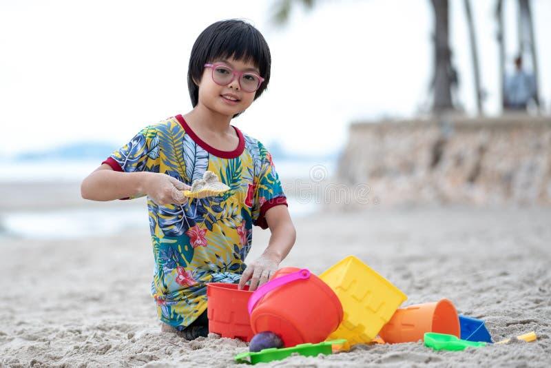 La fille asiatique de portrait avec des lunettes construit le château de sable sur la plage par les modèles colorés image libre de droits
