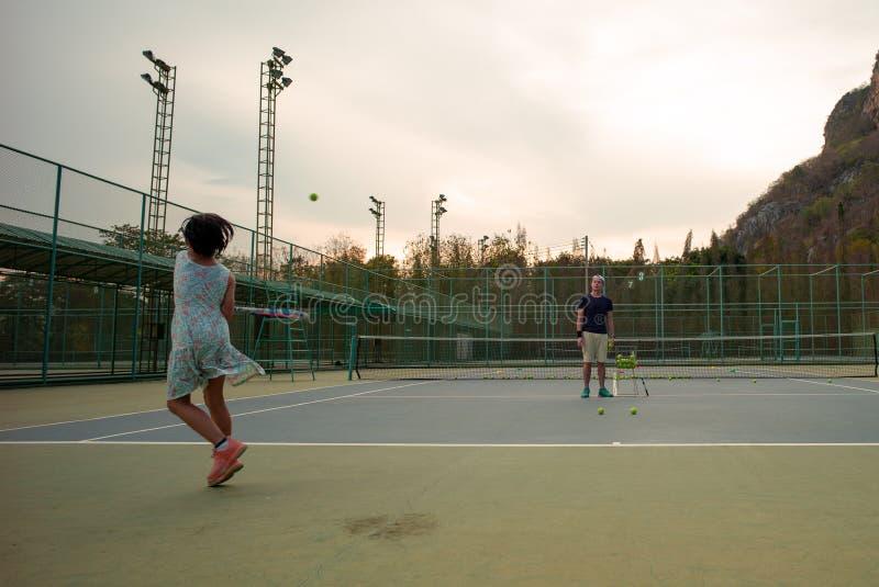 La fille asiatique de portrait joue au tennis avec son père et entraîneur à la cour extérieure avec le fond en pierre de mont photos libres de droits