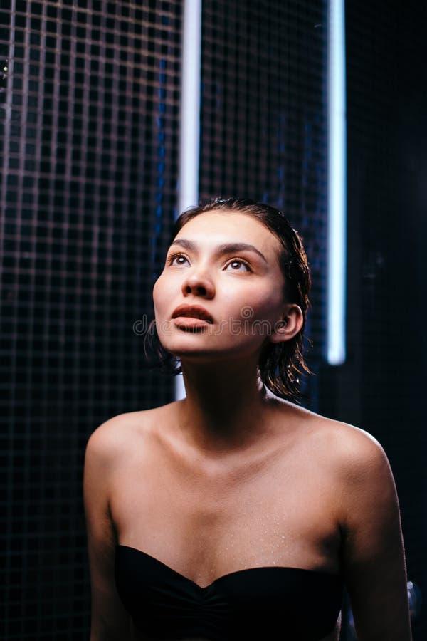 La fille asiatique est fermée à clef dans une petite salle avec les murs noirs photographie stock libre de droits