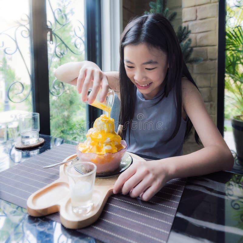 La fille asiatique font l'écrimage pour le bingsu de Msngo photographie stock