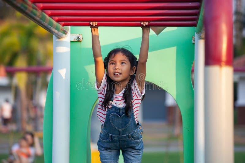 La fille asiatique mignonne d'enfant accrochent la barre par sa main pour s'exercer images stock