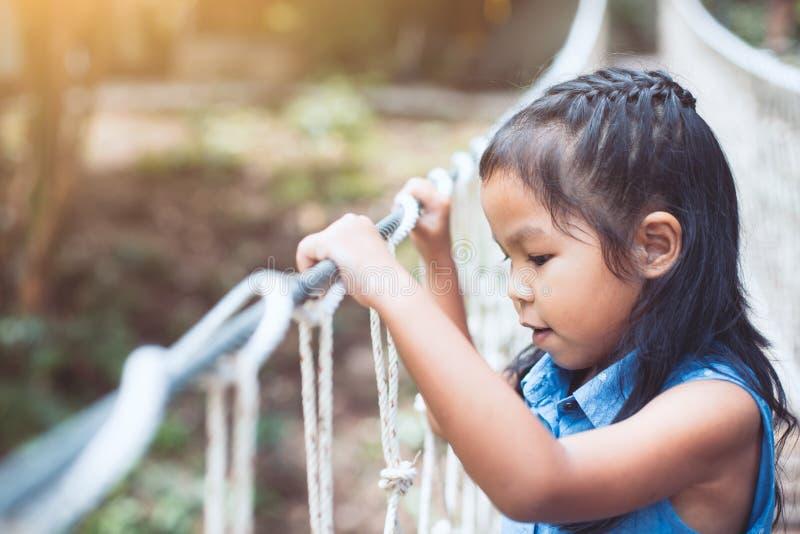 La fille asiatique mignonne d'enfant va sur le pont de cordage d'armement photos stock