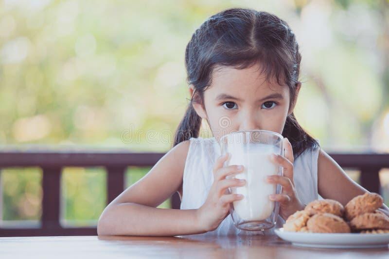 La fille asiatique mignonne de petit enfant boit d'un lait de verre images stock
