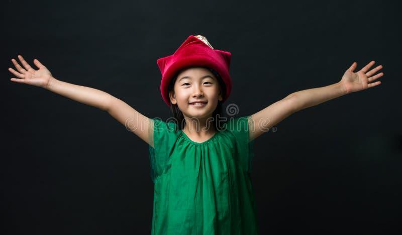La fille asiatique mignonne s'est habillée dans une robe verte avec un chapeau féerique et deux bras grands ouverts sur un fond n photos stock