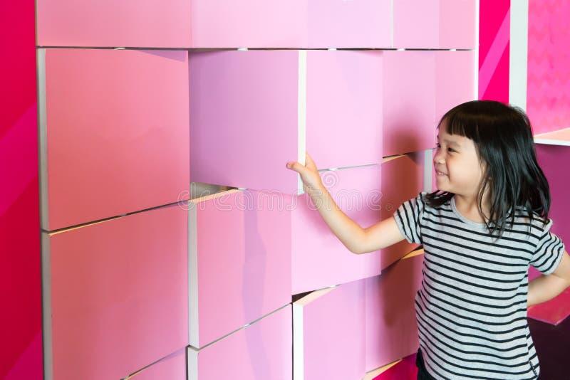 La fille asiatique a plaisir à renverser les panneaux roses de séparation photos libres de droits