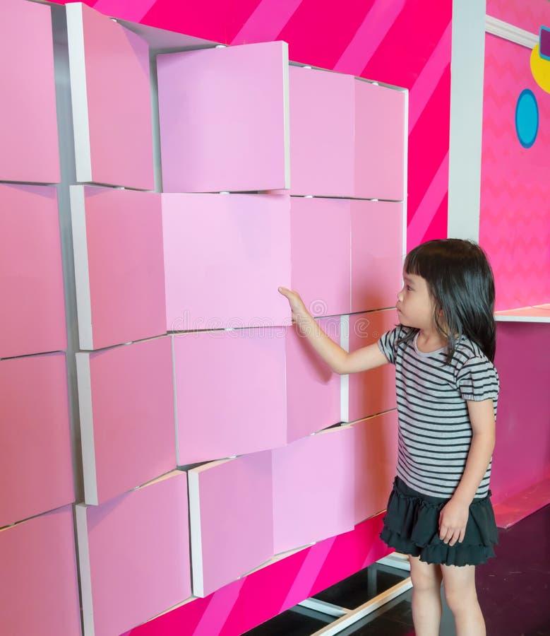 La fille asiatique a plaisir à renverser les panneaux roses de séparation photographie stock