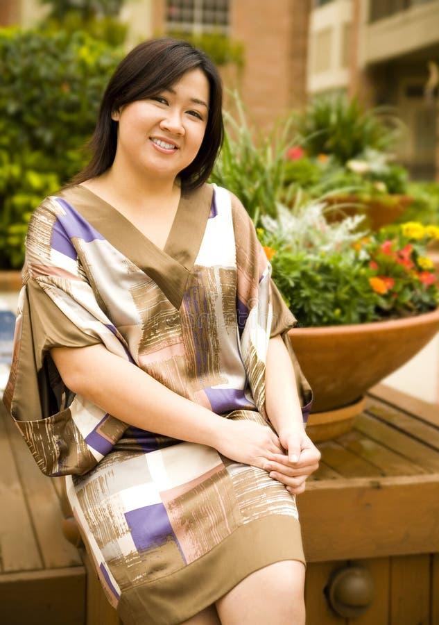 La fille asiatique s'asseyent sur le stationnement image stock