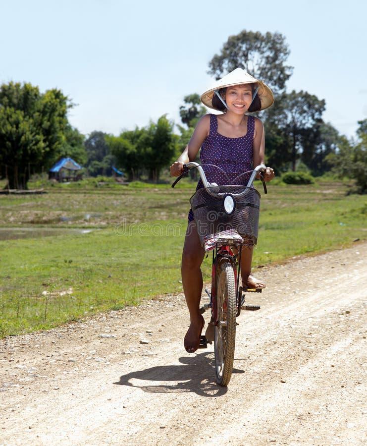 La fille asiatique va sur une bicyclette photographie stock libre de droits