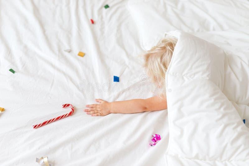 La fille assez adorable se trouve sous la couverture blanche chaude, a les rêves, main de stratches à la sucrerie douce de carame images stock