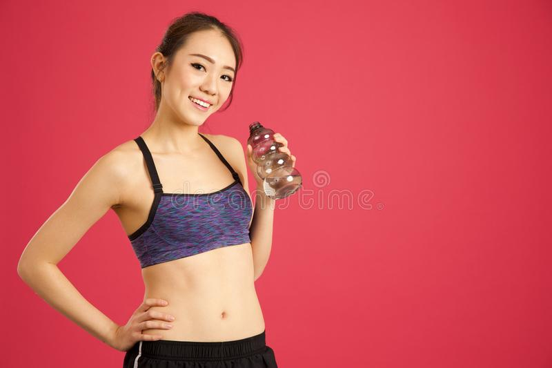 La fille assez asiatique dans la bouteille d'eau potable de studio après établissent images libres de droits