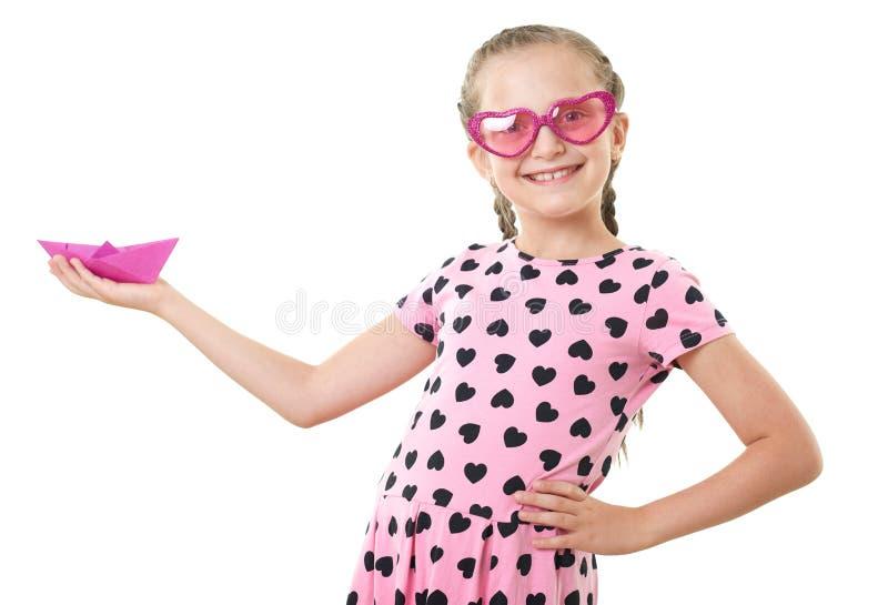 La fille assez petite avec le portrait de papier de studio de bateau, habillé dans le rose avec le coeur forme, le fond blanc image stock