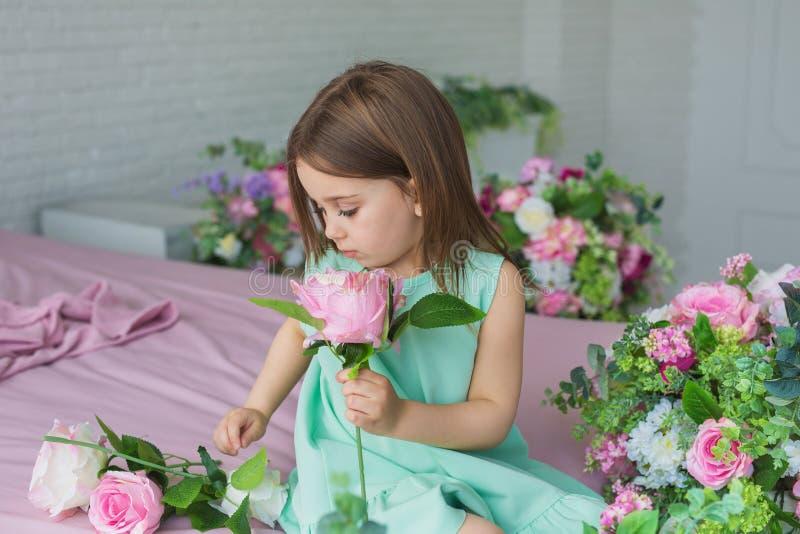 La fille assez petite dans une robe de turquoise repose et tient une fleur dans une main dans un studio photographie stock