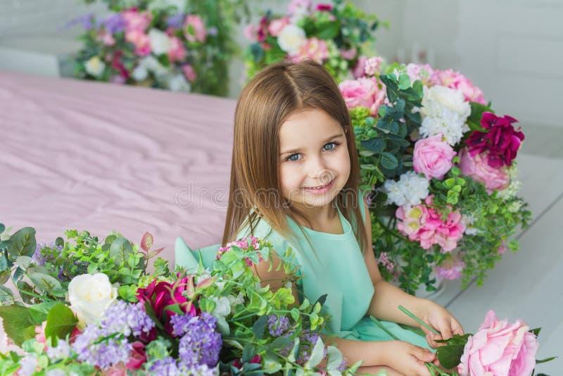 La fille assez petite dans une robe de turquoise s'assied et sourit près de l'des fleurs dans un studio photographie stock