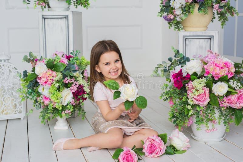 La fille assez petite dans une robe rose-clair s'assied sur un plancher et tient une fleur dans un studio images stock
