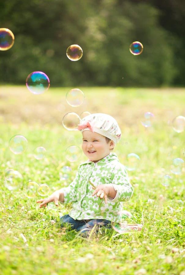 La fille assez petite est riante et jouante avec des bulles de savon image libre de droits