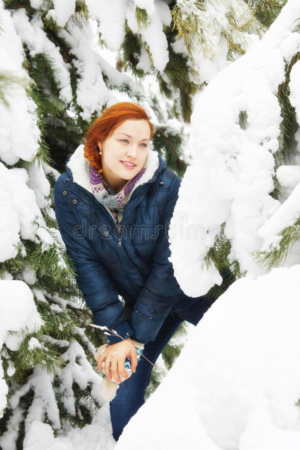 La fille assez rousse heureuse se tient à côté du pin dans une forêt images stock