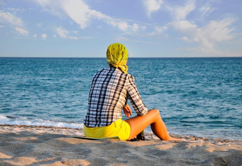 La fille assise regarde sur la mer, à côté de elle est une bouteille de bière images libres de droits