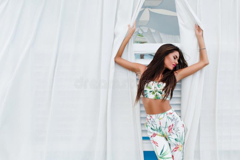 La fille attirante de brune avec de longs cheveux pose entre de longs rideaux blancs extérieurs Elle porte le tissu coloré avec photographie stock libre de droits