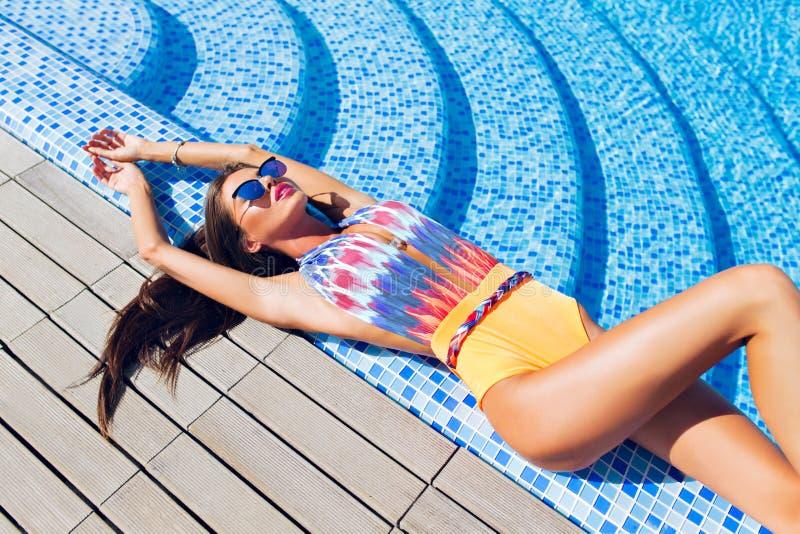 La fille attirante de brune avec de longs cheveux se trouve sur Flor pr?s de la piscine Elle utilise le maillot de bain color?, l image libre de droits