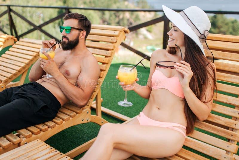 La fille attirante s'assied sur des lits pliants avec le type et regarde vers le bas Elle tient le verre de cocktail et de lunett photos stock