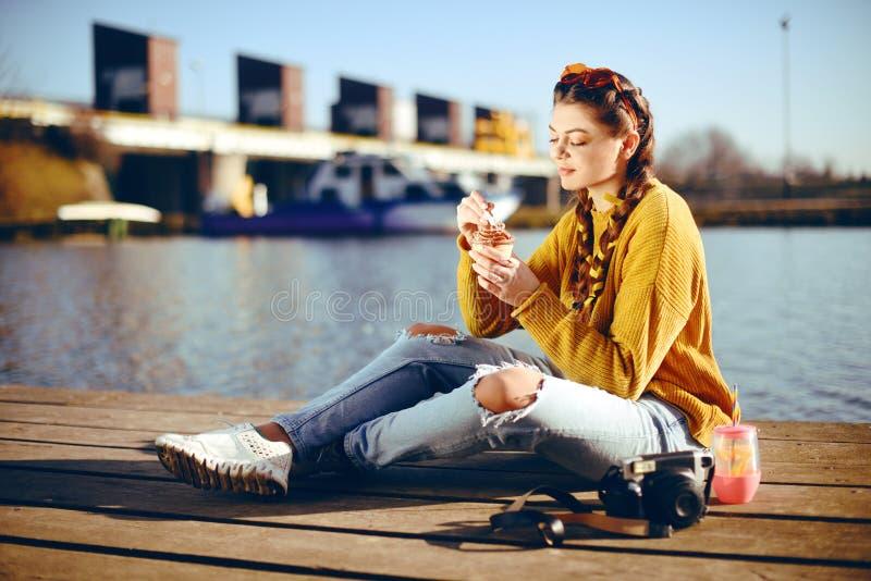 La fille au jour ensoleillé chaud manger la crème glacée  Vibraphone d'été Fille avec les lunettes de soleil jaunes de mode et ha photographie stock libre de droits