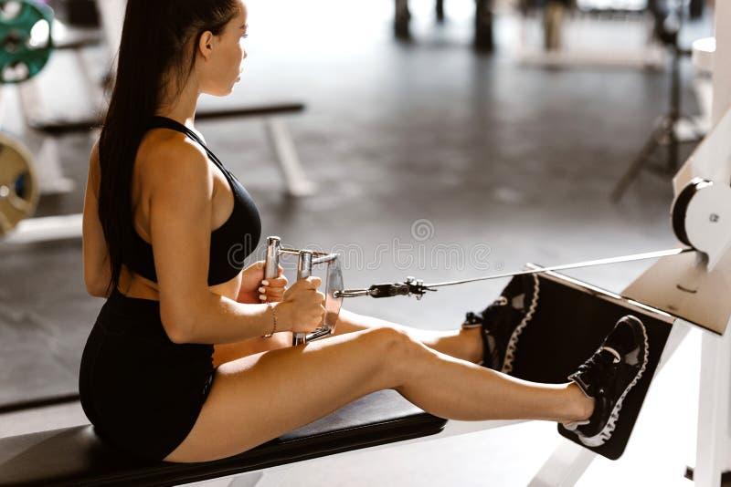 La fille aux cheveux fonc?s mince habill?e dans le dessus et les shorts noirs de sports ?tablit sur la machine d'exercice dans le photos libres de droits