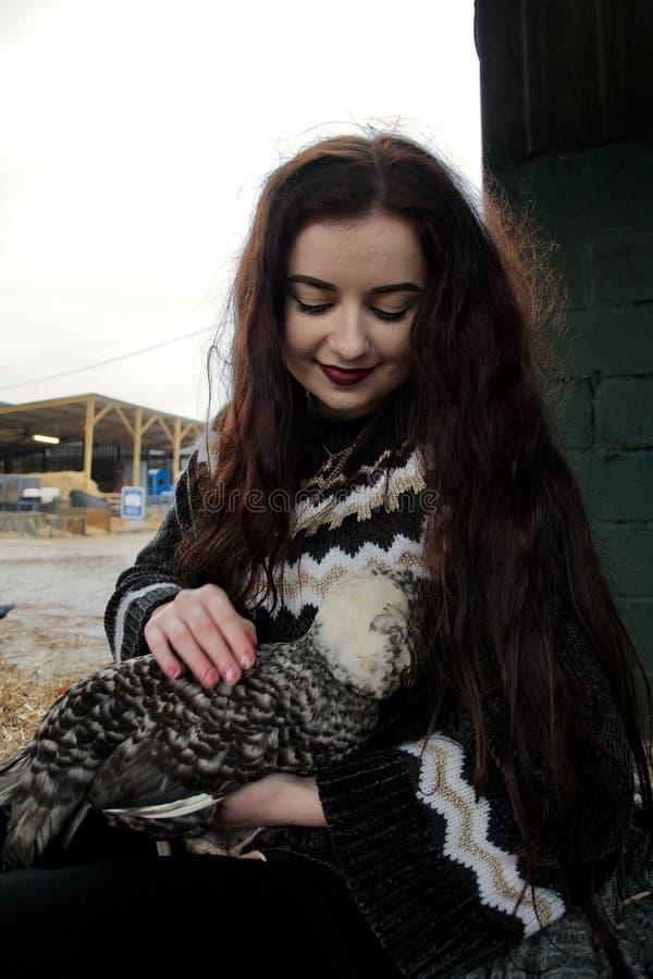 La fille aux cheveux longs à une ferme caresse un poulet pelucheux photographie stock libre de droits
