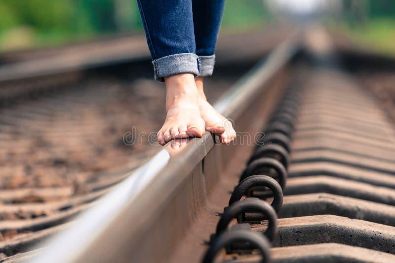 La fille aux pieds nus va par chemin de fer photographie stock libre de droits