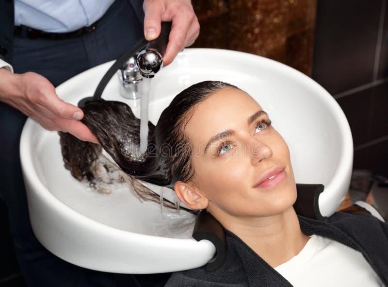 La fille avec de l'eau a rincé le shampooing de la tête photo stock