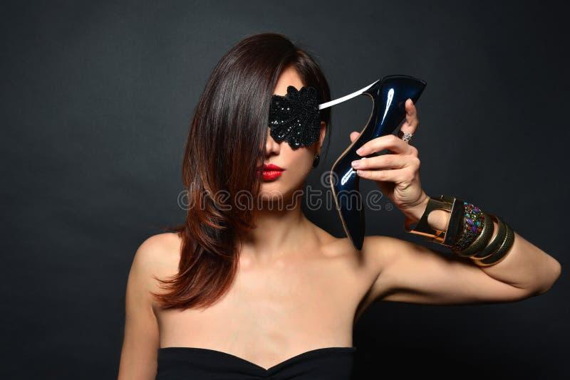 La fille avec de longs cheveux, lèvres rouges et bijoux des bracelets des chaussures à talons hauts noires a mis le talon à so image stock