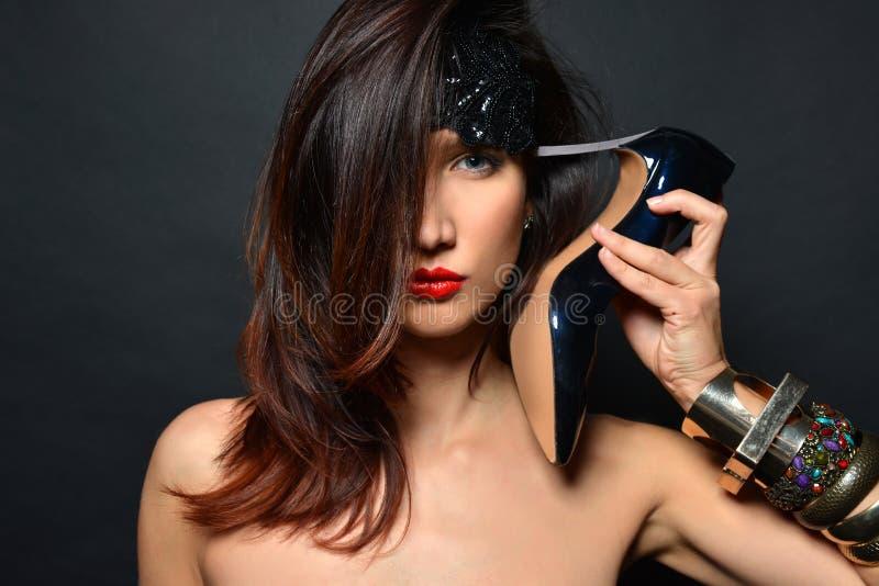 La fille avec de longs cheveux, l?vres rouges et bijoux des bracelets des chaussures ? talons hauts noires a mis le talon ? son t photographie stock