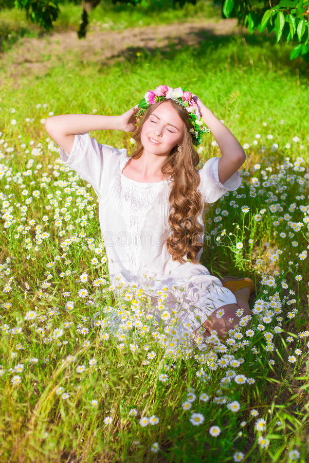 La fille avec de longs cheveux utilisant une couronne des marguerites sur le champ photos libres de droits
