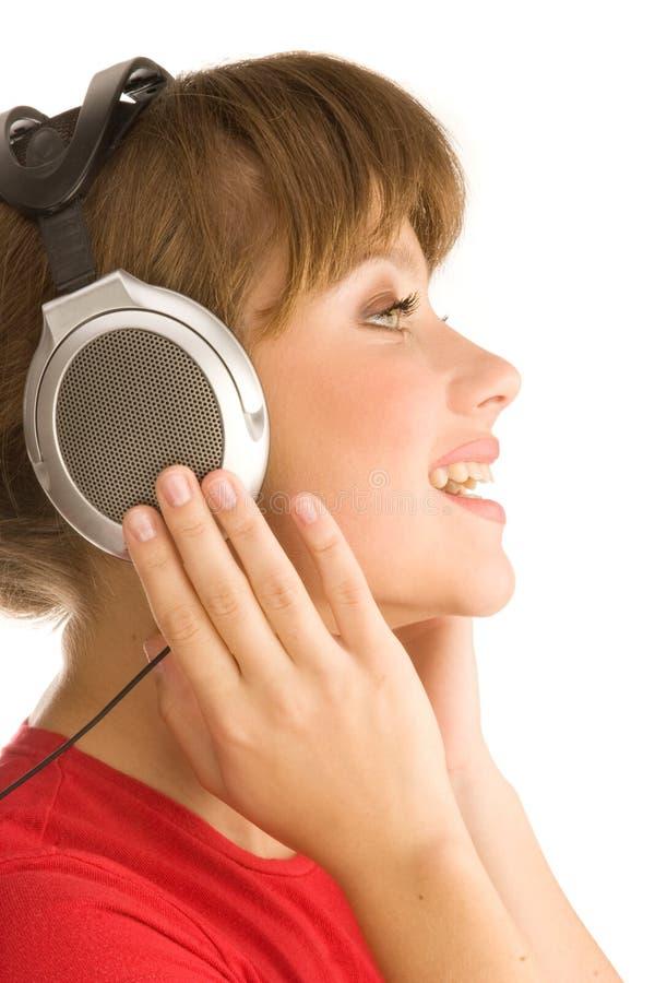 La fille avec des écouteurs chante image stock