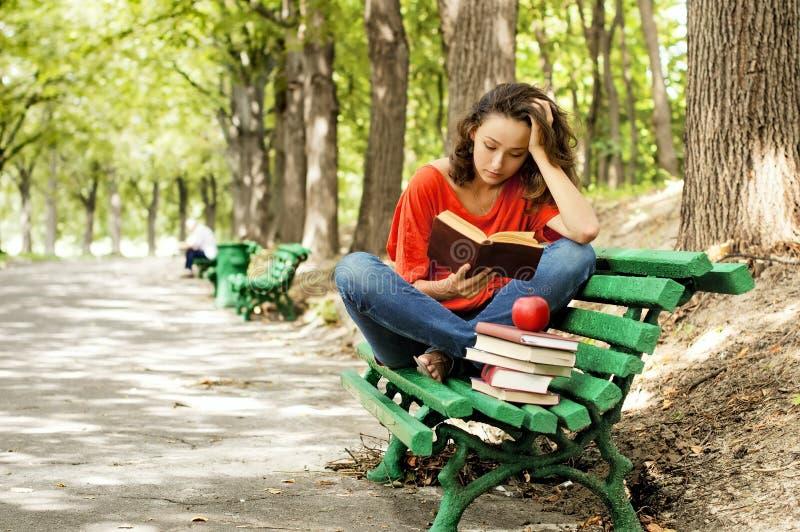 La fille avec des livres se reposant sur un banc image stock