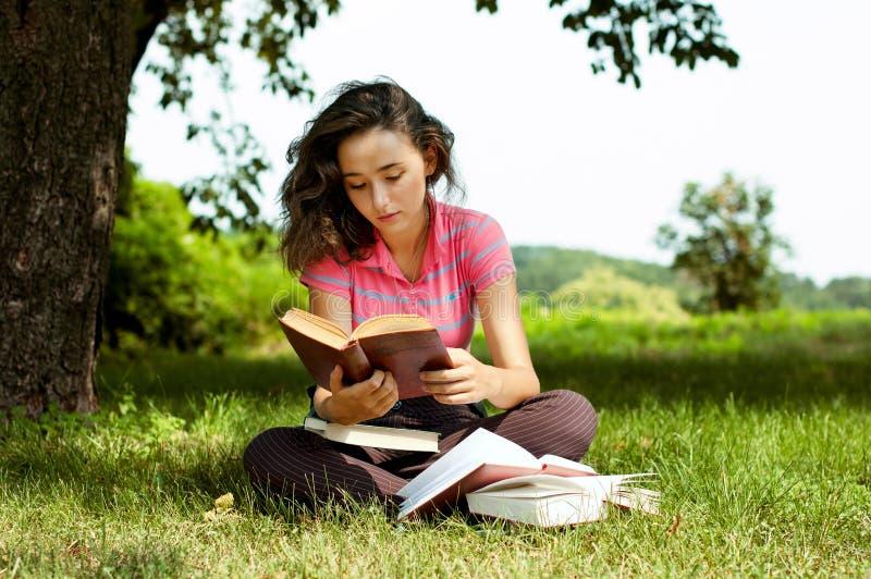 La fille avec des livres se reposant sur une herbe photographie stock