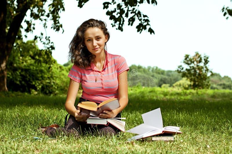 La fille avec des livres se reposant sur une herbe photo libre de droits