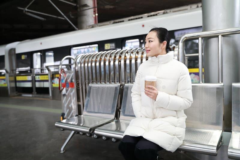La fille avec du café dans sa main s'assied dans une chaise et une métro de attente photo libre de droits