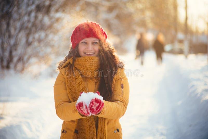 La fille avec du charme dans une guêpe et un chapeau rouge jette la neige dans le ciel photo libre de droits