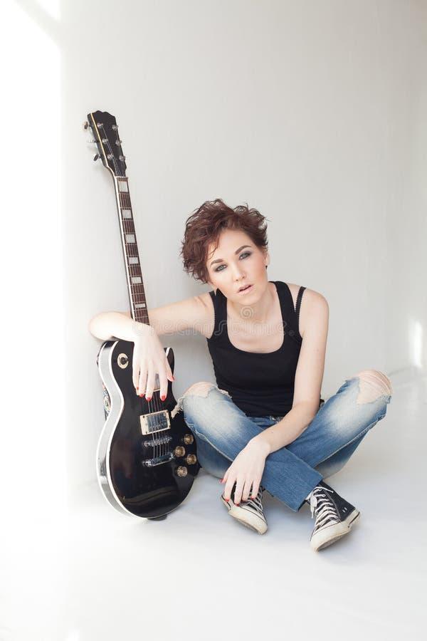 La fille avec la guitare s'assied sur le plancher photo stock