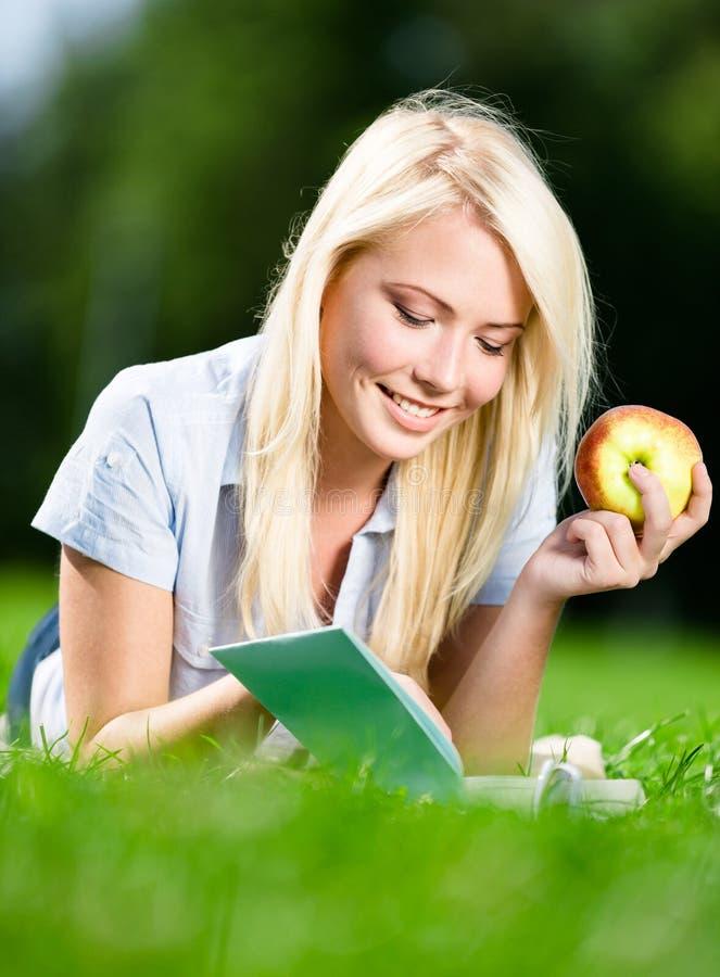 La fille avec la pomme lit le livre se trouvant sur l'herbe photos libres de droits