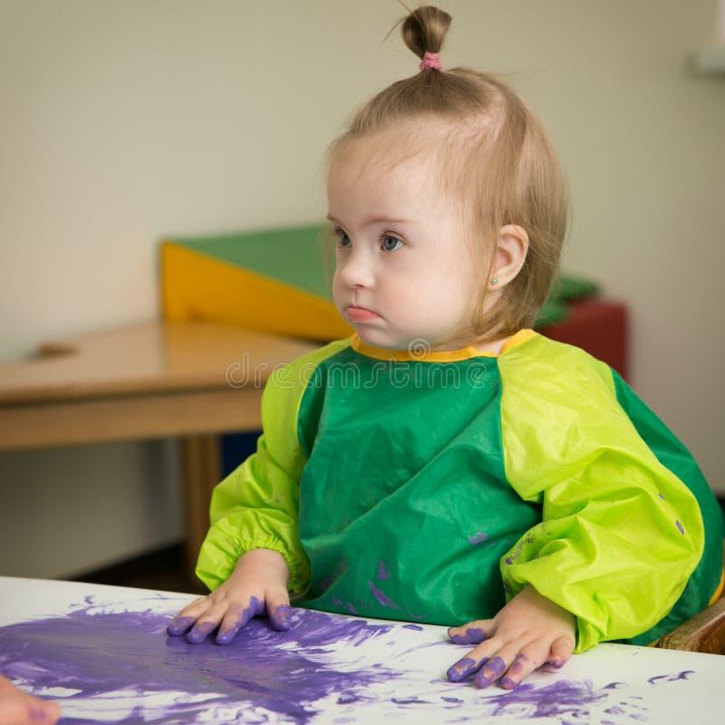 La fille avec la trisomie 21 dessine la peinture de doigts photo libre de droits