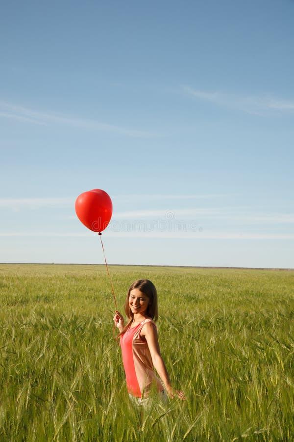 La fille avec le ballon rouge se tient sur le champ photographie stock