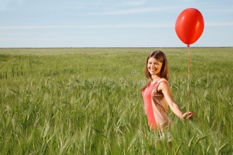 La fille avec le ballon rouge se tient sur le champ images stock