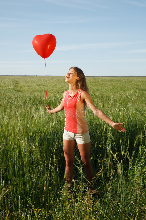 La fille avec le ballon rouge se tient sur le champ photo libre de droits