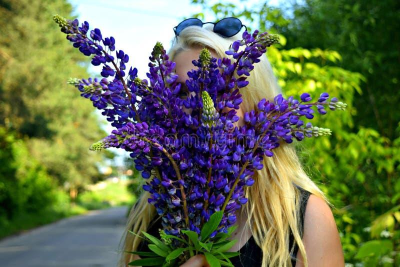 La fille avec le bleu fleurit des lupins en nature photo stock