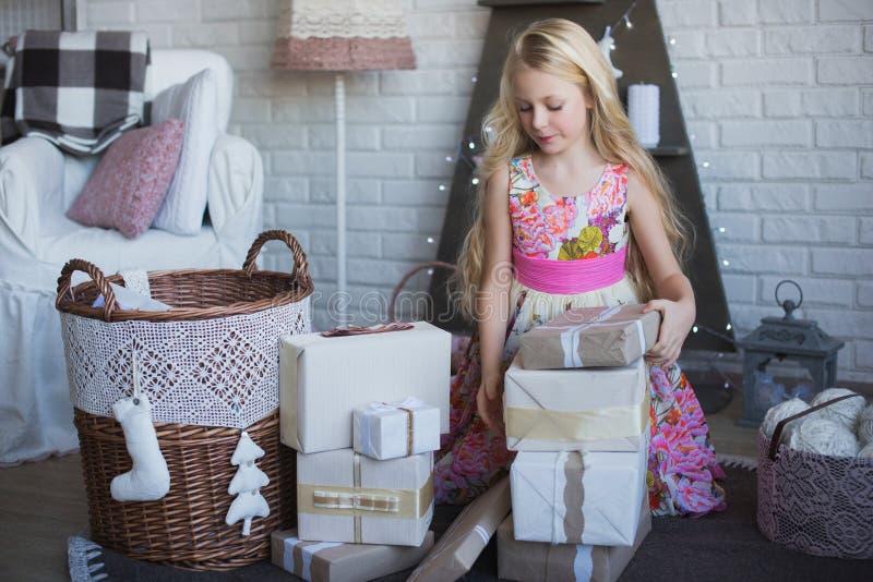 La fille avec le boîte-cadeau dans des mains est heureuse considère la préparation pour les vacances, emballage, boîtes, Noël, no images stock