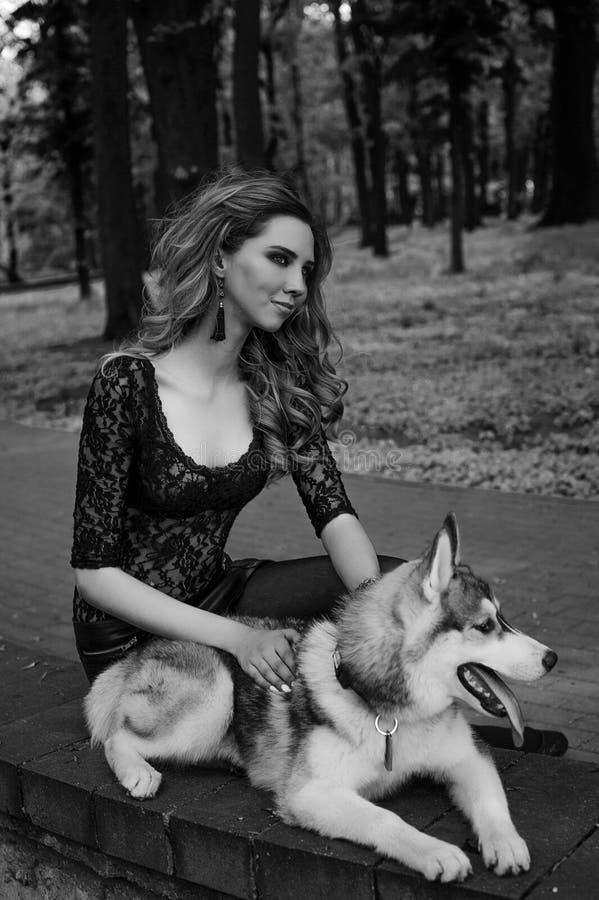 La fille avec le chien de traîneau sibérien Jeux délicieux de fille avec un chien de traîneau sibérien Fille marchant avec un chi photo stock