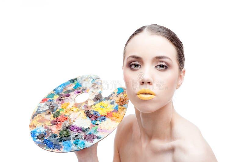La fille avec le maquillage d'imagination tient une palette photos stock