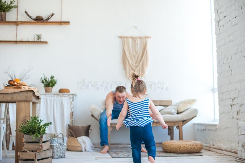 La fille avec le père dans la chambre de la cuisine jouent Relations dans la famille Petite fille jouant avec le papa images libres de droits