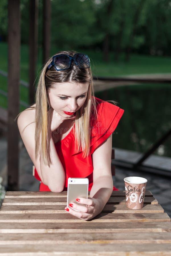 La fille avec le rouge à lèvres lumineux dans une robe rouge s'assied à une table le soir dans un café pour une tasse de café photographie stock libre de droits